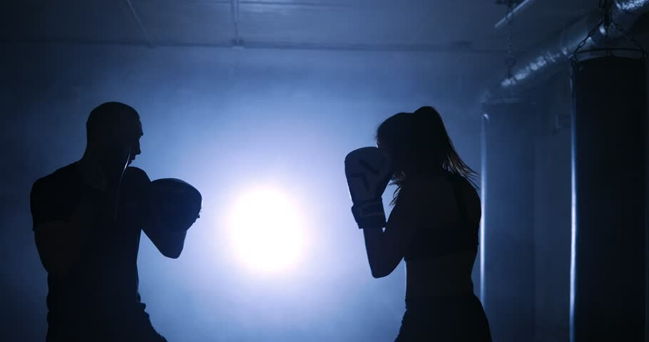 Silhouettes of a female boxer punching a boxing bag with boxing gloves in a smoky gym