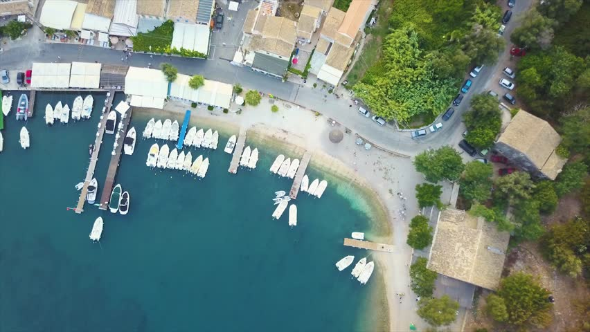 Aerial bird's eye view video taken by drone of picturesque harbour and beach on the beautiful island of Corfu, in Greece in the Mediterranean.  | Shutterstock HD Video #1008789932