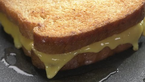 Clip of grilled cheese sandwich on flat top griddle with slider action and sizzling audio.