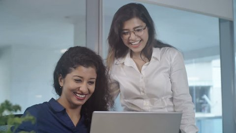 Two young and attractive office female employees/workers working together on a laptop in a modern office space are smiling and  celebrating their success after completing a huge task or business deal