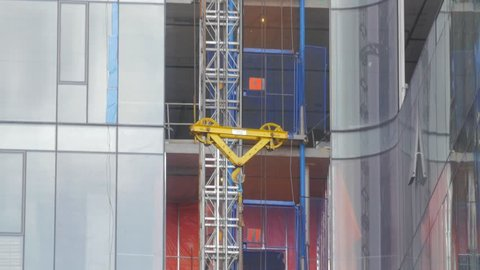Construction Workers making progress on a high rise condo development with an active crane pulley hoist lift raising an object.