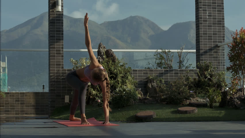 Closeup young girl changes yoga exercises on rest terrace decorated with green lawns and plants | Shutterstock HD Video #1008816602