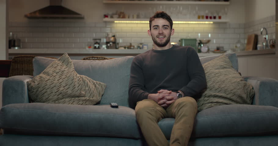 Young, attractive man sits down on a couch and turns on the television using a remote control. | Shutterstock HD Video #1008851162