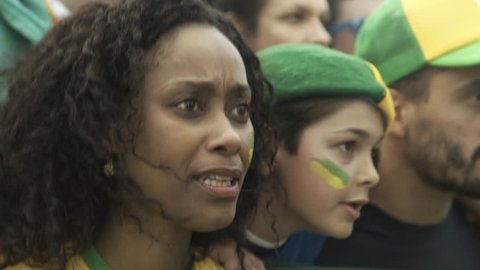 Brazilian soccer fans watching match at stadium with look of disappointment
