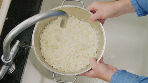 Closeup Of Man Washing White Rice In Colander At Sink