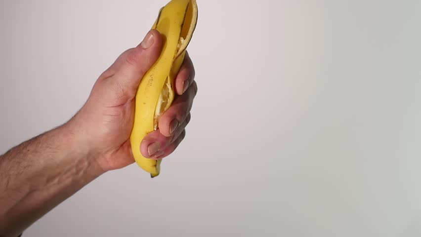 Vitamin and healthy eating. Ripe mellow banana fruit squeezed, mashed, or crushed with yellow skin and flesh drops, splashes, on white background