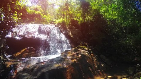 Water flows and tumbles over the brink of a natural waterfall in this tropical jungle wilderness in Phuket. Thailand.