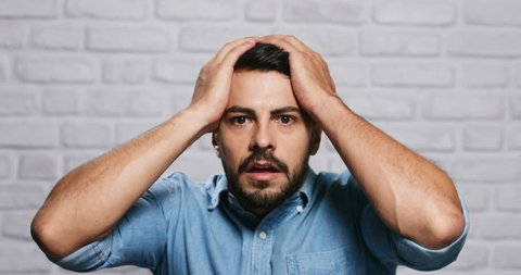 Portrait of upset man against white wall as background. Italian guy getting bad news, touching head with hands.