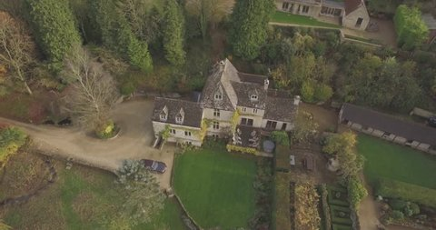 Establishing aerial shot of a quiet country house in Cotswolds, UK in autumn