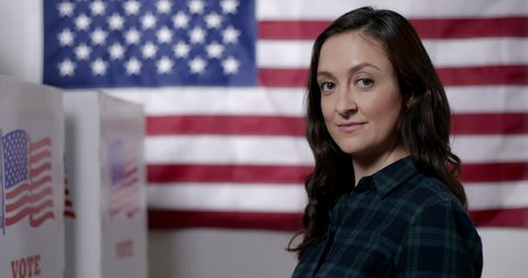 "MCU profile Caucasian American woman in plaid shirt puts on ""I Voted"" sticker while standing proud in front of US flag next to polling booths."