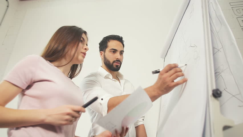 Two intelligent and lovely office workers preparing for the training, solving maths tasks while writing on the whiteboard, long-haired woman wearing casual pink shirt, bearded man - pristine white | Shutterstock HD Video #1009035992