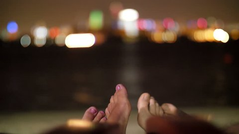 Young couples legs, feet of two lovers on the beach near the water, at night, against lights of city skyscrapers, the shines of the lights