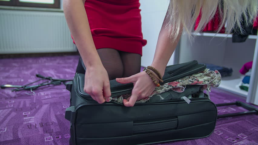 Young woman closing the full suitcase with zipping the zippier Footage is taken in slow motion. | Shutterstock HD Video #10090382