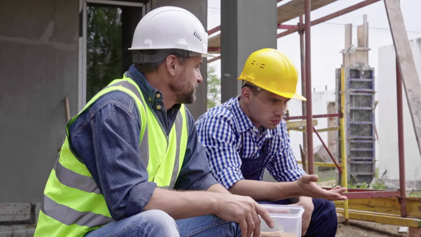 Medium shot of two male engineers in hard hats taking break from work, talking to each other and eating food from lunch box
