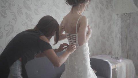 Bridesmaid tying bow on wedding dress. Bride getting ready for the wedding ceremony. Wedding dress close-up