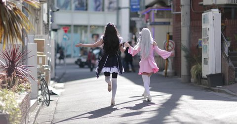 Japanese female friends dancing in street, Harajuku, Tokyo, Japan
