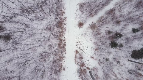 Man running on white winter forest road, top view drone aerial footage with runner moving from top to bottom. Inspiring fitness and motivation concept. Gimbal stabilized footage. Shot with 4K DLOG.
