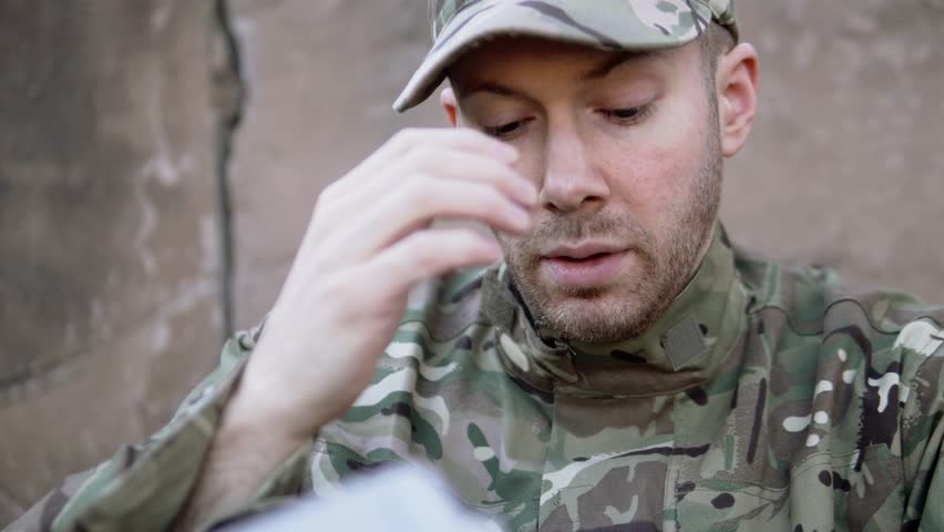 Male Soldier Fights Back The Tears, Missing Wife And Family. He Looks Through Letter And Photographs. Homesick And Sad Military Man. Part Of A 4K Army Collection.