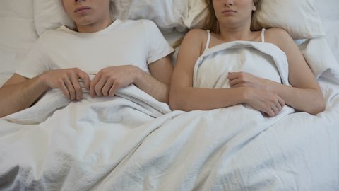 Young male and female lying in bed feeling embarrassed, erectile dysfunction