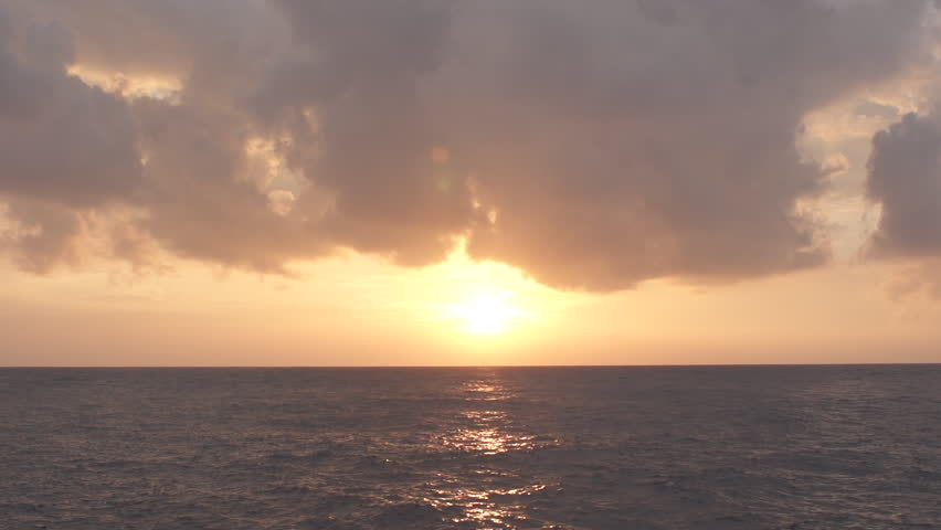 Slow Motion Of Setting Sun Above The Tranquil Open Ocean And Cloudy Sky | Shutterstock HD Video #10091462