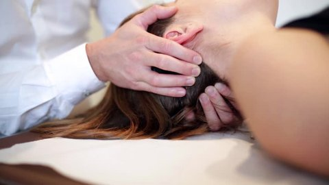 Woman having chiropractic back and neck adjustment