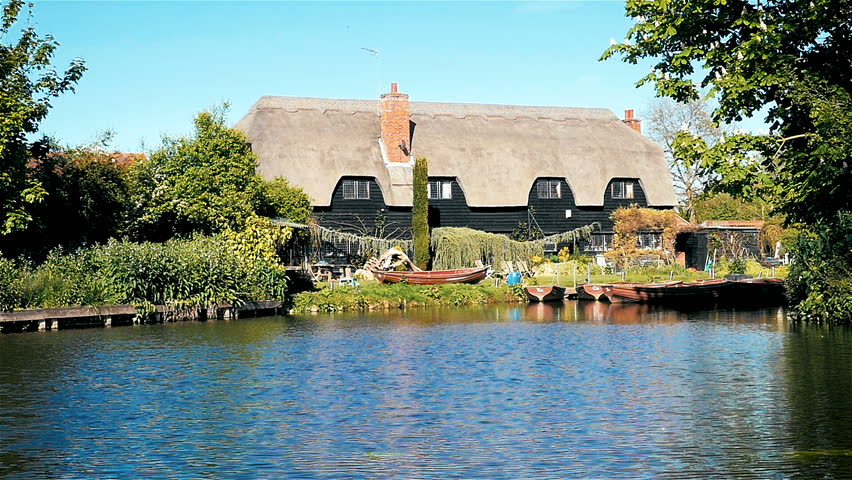 Thatched cottages and boathouse on the River Stour, Suffolk, England. A tranquil rural English view on the banks of the River Stour in the heart of English landscape painter John Constable country.