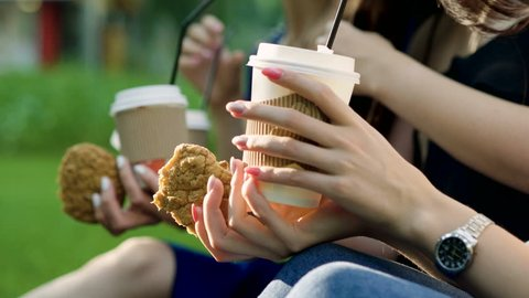 Close-up of three young women drinking beverages and eating pastries in a park. 4K