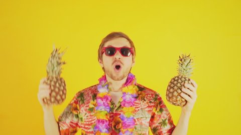 Happy tourist with hawaiian shirt and two pineapples dancing in slow motion