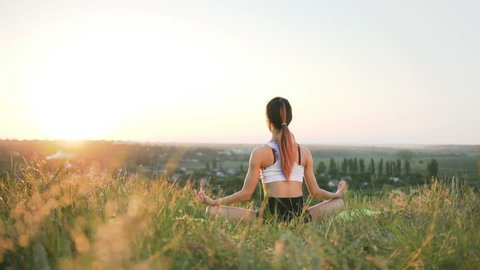 Slender girl doing yoga in the field at sunset. Outdoor healthcare. Wide shot