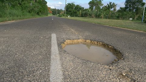 LOW ANGLE, CLOSE UP: Large gaping pothole filled with muddy water sticks out of empty road leading through sunny tropical island. Deteriorating concrete street is becoming filled with large holes.