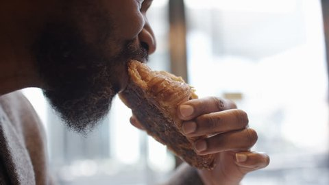 Mature black man in a suit takes a bite from his almond croissant