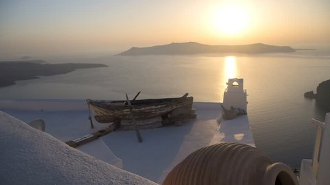 Cinemagraph 4K resolution - Old boat on a white roof in Fira, Santorini with view of the volcano island on the background