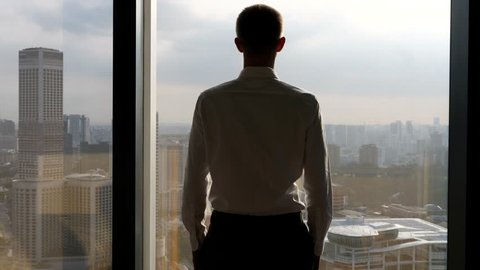 Businessman Looking At City From Office