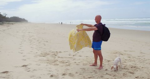 Man shaking and folding his beach towel
