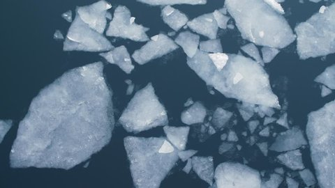 Cracked Ice floes slowly drifting through the dark water of the Copenhagen canal - filmed from above