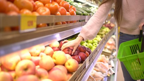 Woman selecting fresh red apples in grocery store supermarket sale, shopping marketplace food taking choosing apples girl with bag buying apples at shopping basket. 4 k apple fruits Woman's hand shop