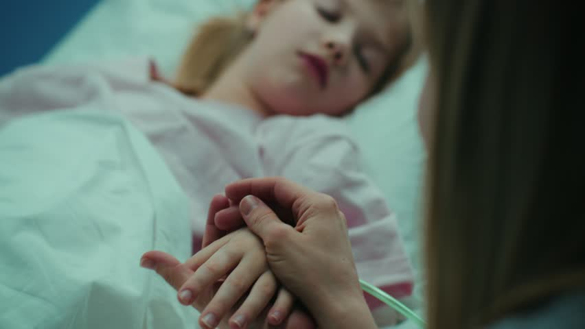 Mother Takes and Holds Hand of Her Sick Little Girl who Is Sleeping in the Hospital Bed. Sad and Hopeful Emotional Moment in Pediatric Ward. Shot on RED EPIC-W 8K Helium Cinema Camera. | Shutterstock HD Video #1009293512