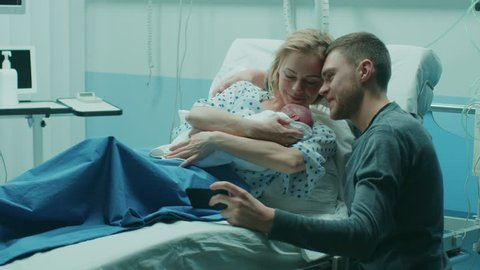 Father Takes Selfie of Him with His Wife Holding Newborn Babie while Lying on the Hospital Bed. Happy Young and Smiling Family. Shot on RED EPIC-W 8K Helium Cinema Camera.
