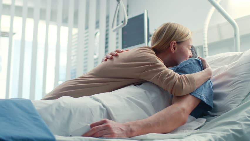 In the Hospital, Happy Wife Visits Her Recovering Husband who is Lying on the Bed. They Lovingly Embrace and Smile. Shot on RED EPIC-W 8K Helium Cinema Camera. #1009295552