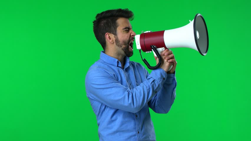 Man shouting with a megaphone over a green screen background