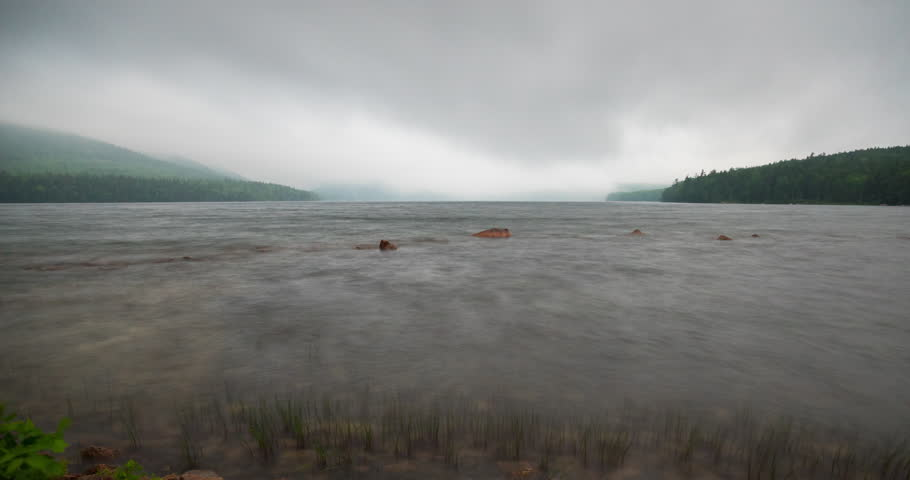 A static time lapse of clouds and fog passing over Eagle Lake in Acadia National Park, Maine.