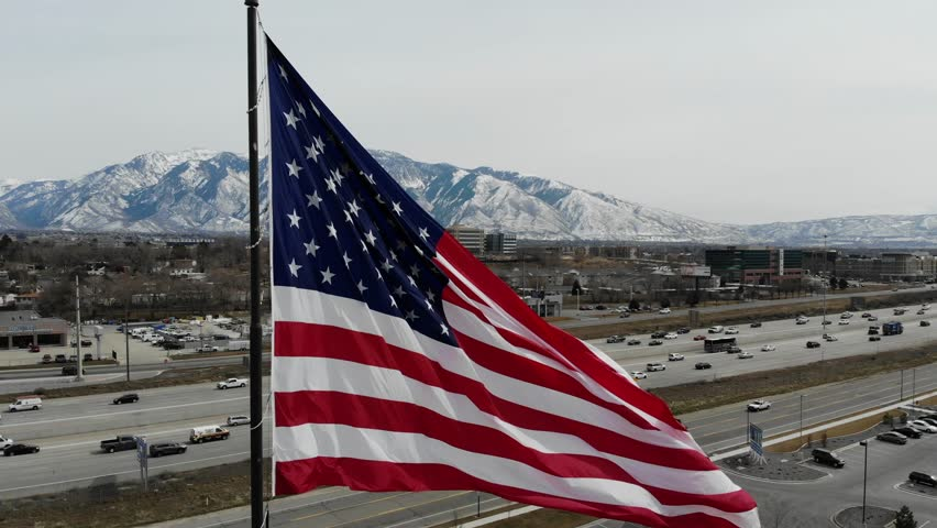 Aerial view of a giant American flag blowing in the breeze with a beautiful snowy mountain landscape in the background.