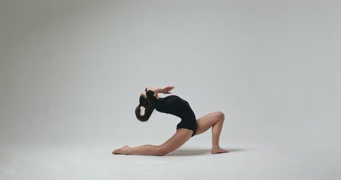 Young female ballet dancer stretching. Video clip of young barefoot female ballet dancer stretching in studio.