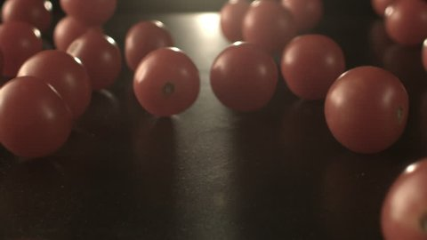 A slow motion clip of tiny cherry tomatoes bouncing against dark background and rolling down.