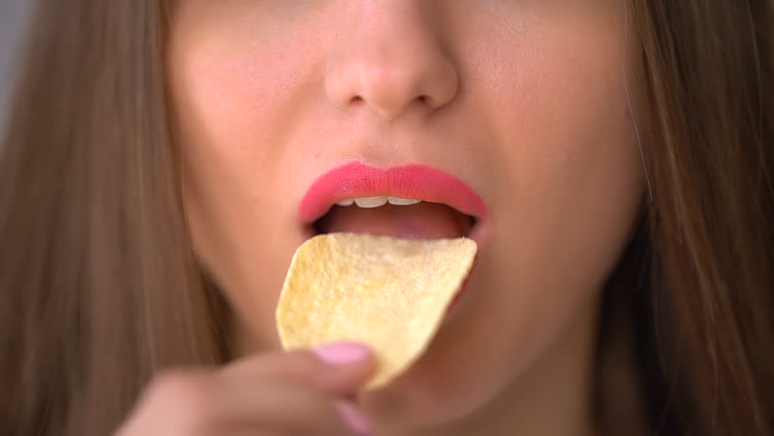 Woman eating chips close-up. Eating Food. fast food. unhealthy diet, overweight, TRANS fats, unhealthy eating, slow-motion