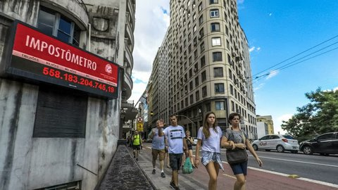Sao Paulo, Brazil, March 24, 2018. Impostometro (panel with taxes paid in the country) and people walk on Boa Vista Street in downtown Sao Paulo, Brazil