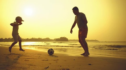 Father and son playing together with ball in football on the beach under sunset background