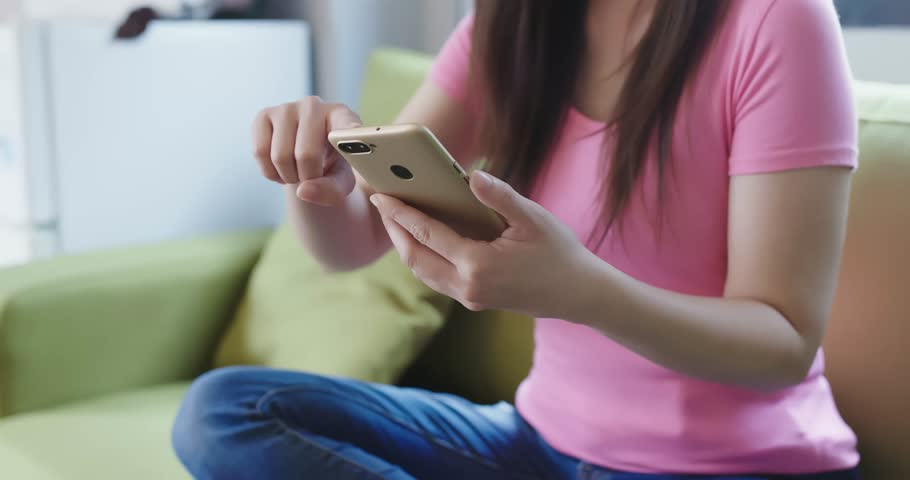Woman use phone and sit on sofa at home | Shutterstock HD Video #1009417502
