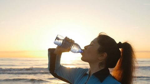 Woman drinking from a Water Bottle at Sunset near sea