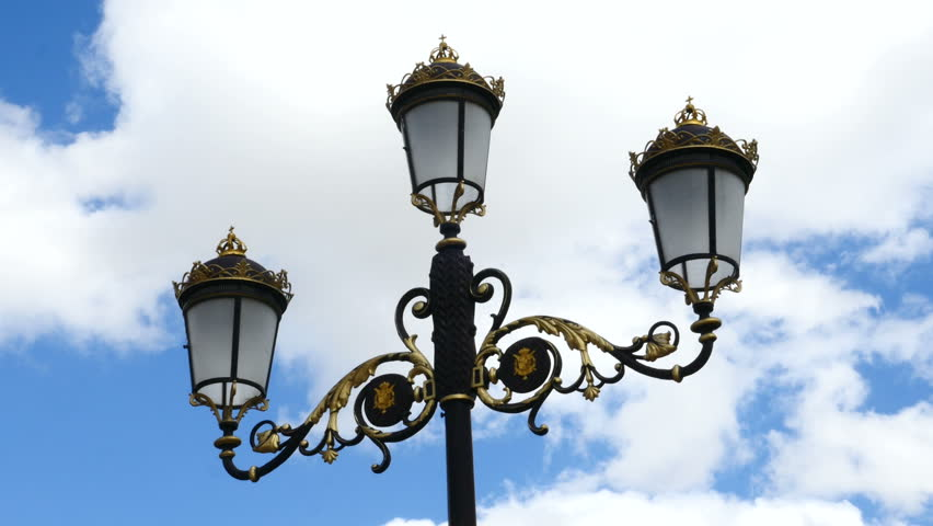(TIME LAPSE) detail of a lamppost with three black and gold lamps. Filmed on April 4, 2018 in a park in Madrid, Spain.